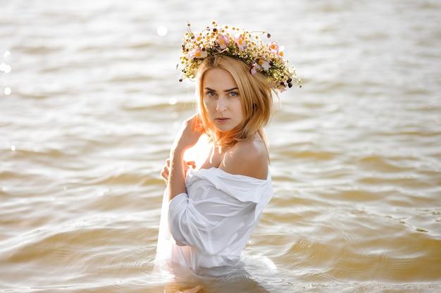 Aktbild der attraktiven blonden frau im blumenkranz