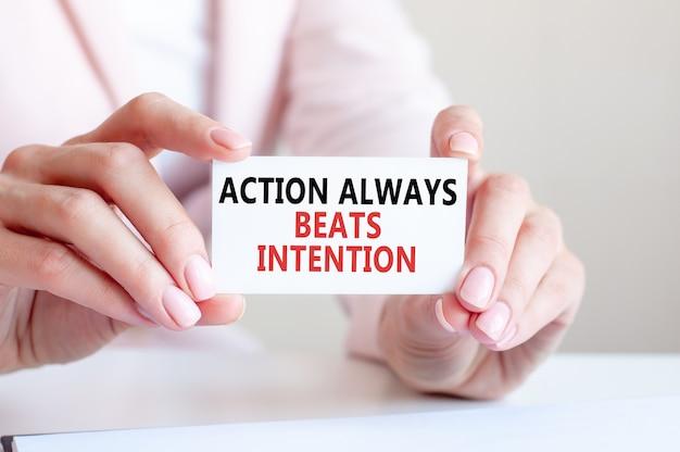 Aktion schlägt immer absicht ist auf einer weißen visitenkarte in den händen einer frau geschrieben.