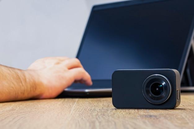 Aktionskamera auf dem tisch vor dem hintergrund eines mannes, der an einem laptop arbeitet.