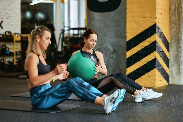 Aktiv bleiben zwei junge kaukasische athletische frauen in sportbekleidung, die mit fitnessball im fitnessstudio trainieren