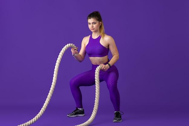 Aktiv. schöne junge sportlerin üben, einfarbiges lila porträt. sportliches kaukasisches fit-modell mit seilen. bodybuilding, gesunder lebensstil, schönheits- und aktionskonzept.