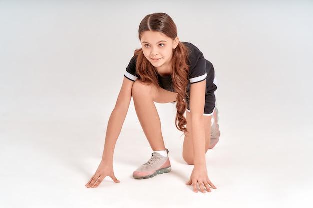 Aktiv sein in voller länge eines süßen teenager-mädchens in sportkleidung, das in startposition steht und lächelt