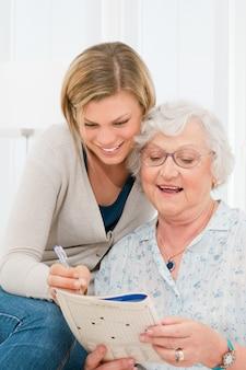 Aktive ältere dame, die mit hilfe ihrer jungen enkelin kreuzworträtsel löst