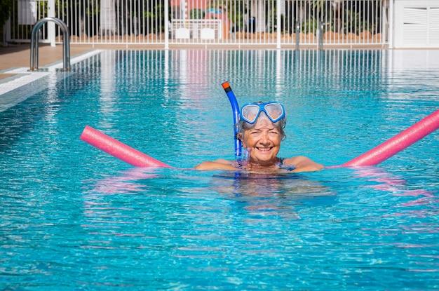 Aktive ältere frau, die im schwimmbad mit schwimmnudeln trainiert glückliche rentner