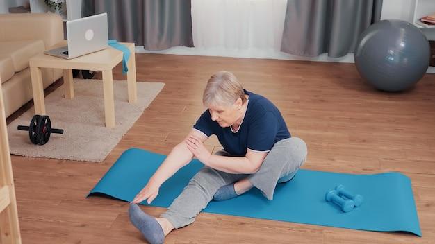 Aktive ältere frau, die körper auf yogamatte ausdehnt. seniorenrentner trainieren zu hause sportaktivitäten im rentenalter