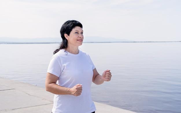 Aktive ältere frau, die nahe dem flussufer joggt