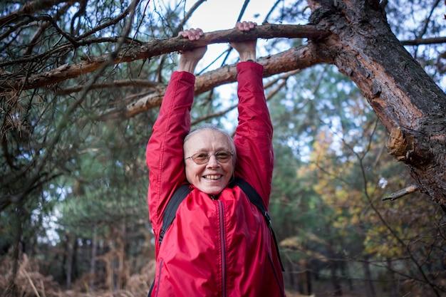 Aktive ältere frau glücklich, vom baum im wald zu hängen