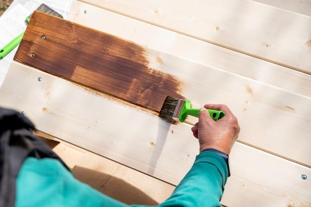 Aktive ältere frau malt einige holzstücke, holz durch braune farbe farbe mit pinsel. arbeiter malt eine holzwand