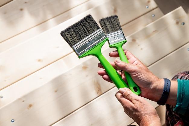 Aktive ältere frau malt holzstücke, holz durch braune farbe farbe mit pinsel. arbeiter malt eine holzwand,