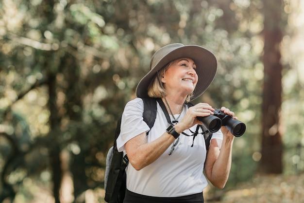 Aktive ältere frau mit fernglas, um die schönheit der natur zu sehen