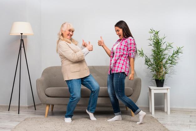 Aktive ältere frau und ihre junge tochter, die daumen herauf zeichen im wohnzimmer zeigt