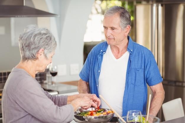 Aktive ältere paare, die einen salat zubereiten