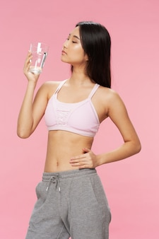 Aktive asiatische frau mit einem glas wasser