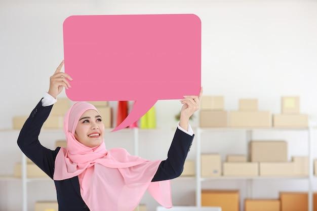 Aktive asiatische muslimische frau im blauen anzug stehend und hält rosa sprechblase