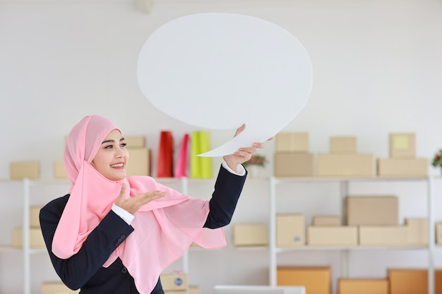 Aktive asiatische muslimische frau im blauen anzug stehend und hält weiße sprechblase mit online-paketbox-lieferung
