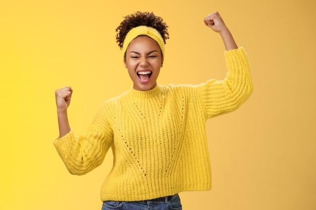 Aktive ausgehende selbstbewusste, fröhliche afroamerikanische weibliche fan-platz-wette, die hoffentlich das team zum sieg ermutigt, steht erhobene fäuste, die den sieg feiern und die geste stolz schreien, gelber hintergrund.