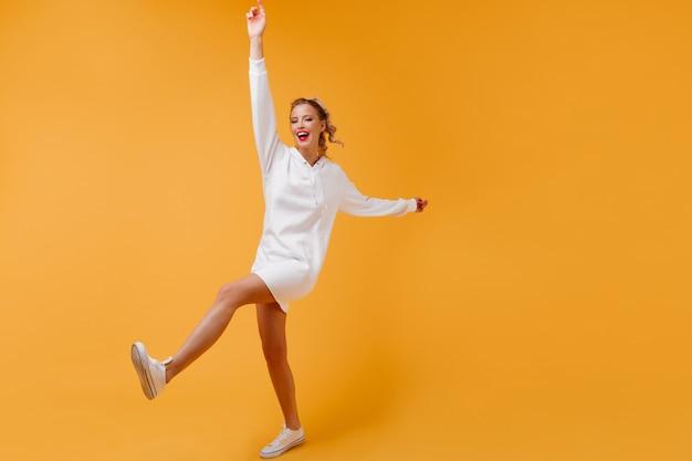 Aktive dame mit schlanken beinen, die sich im orangefarbenen raum bewegen