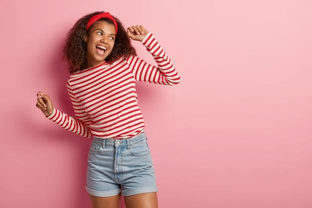 Aktive energetisierte teenager-mädchen mit lockigem haar posiert in gestreiften roten pullover
