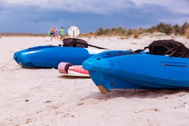 Aktive erholung, sport, kajak. boot zum rafting auf dem wasser. ein paar kajaks stehen an einem sandstrand.