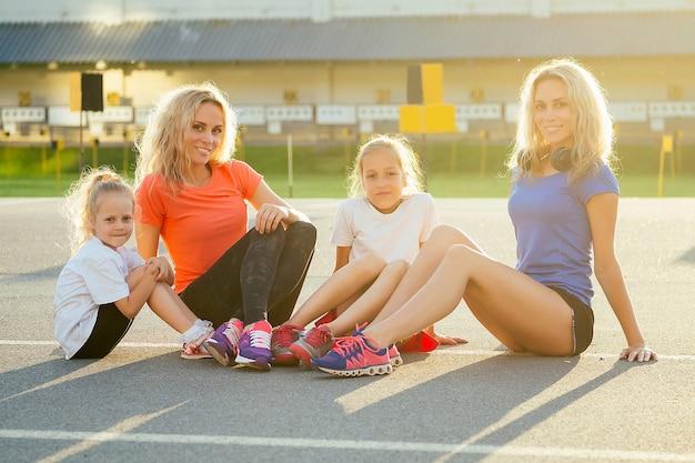 Aktive familie im freien. zwei blonde zwillingsschwestern mutter und ihre töchter in stylischer sportkleidung ruhen auf dem asphalt im stadion. gruppe von vier mädchen im park