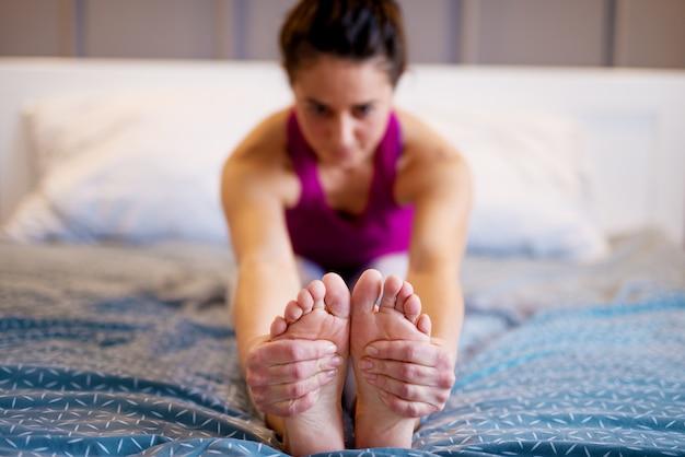 Aktive flexible frau mittleren alters, die yoga-übung streckt, während sie vorwärts auf dem bett sitzt, während ihre hände die füße halten. konzentrieren sie sich auf die füße und hände.