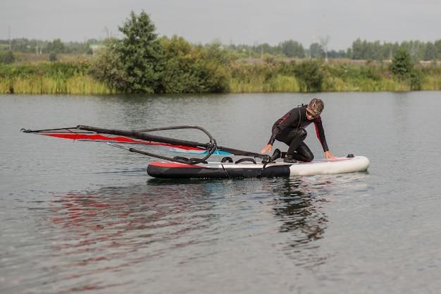 Aktive frau 65 jahre im neoprenanzug beim windsurfen