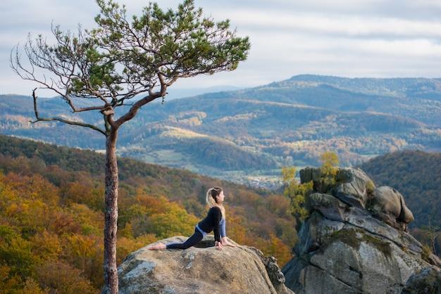 Aktive frau des active übt yoga auf die oberseite des berges nahe großem baum