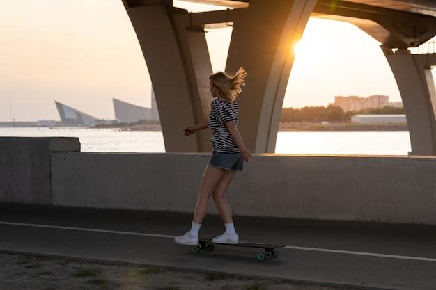 Aktive frau, die am sommerabend schlittschuhlaufen auf longboard entlang des flusses mit blick auf die stadt und den sonnenuntergang genießt