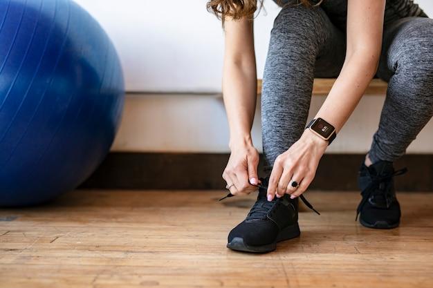 Aktive frau, die eine smartwatch trägt und ihre schnürsenkel bindet