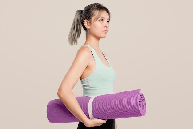 Aktive frau, die eine yogamatte hält