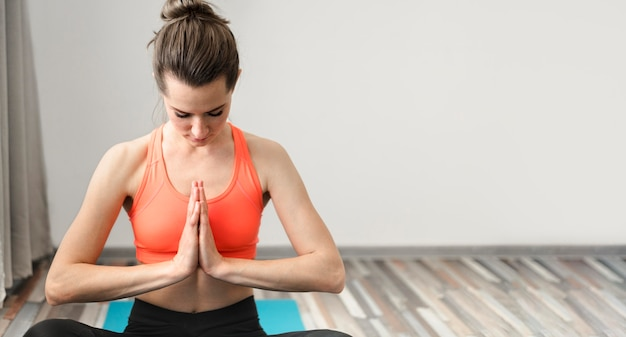 Aktive frau, die yoga zu hause ausübt