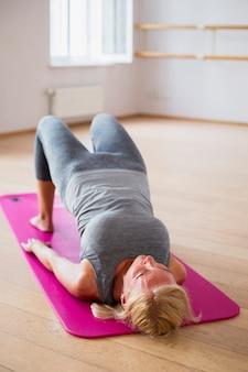 Aktive frau, die yogapositionen ausübt