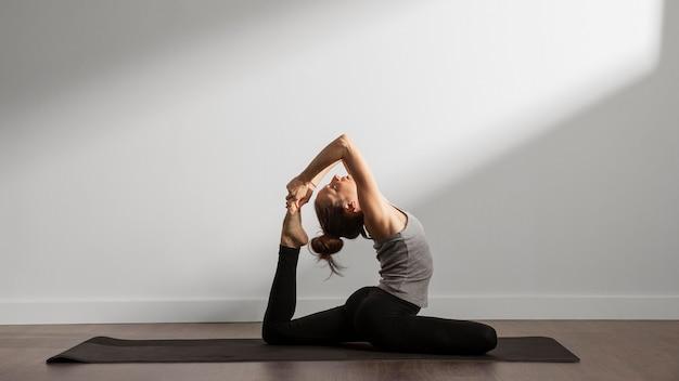 Aktive frau, die zu hause yoga praktiziert