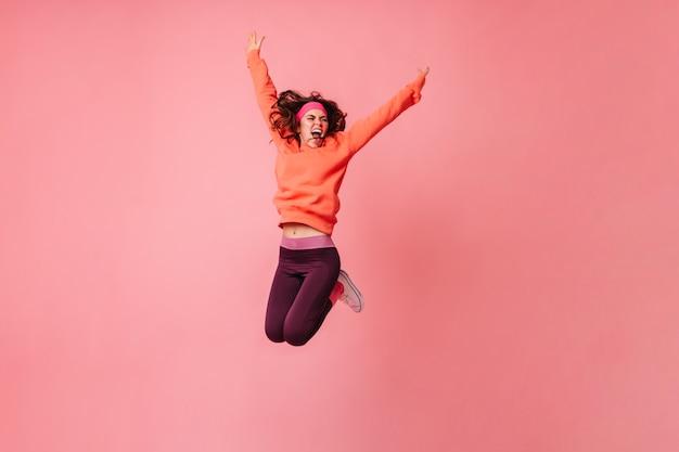 Aktive frau in orangefarbenem hoodie und dunklen leggings, die kräftig auf rosa wand springen