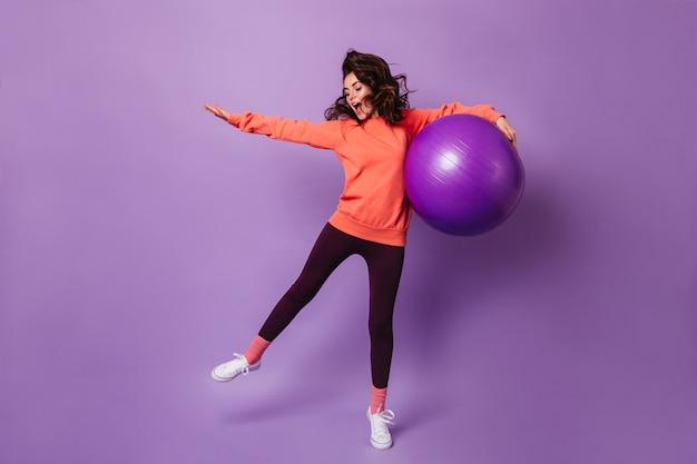 Aktive frau in schwarzen leggings und orange hoodie, die mit fitball auf lila wand springt
