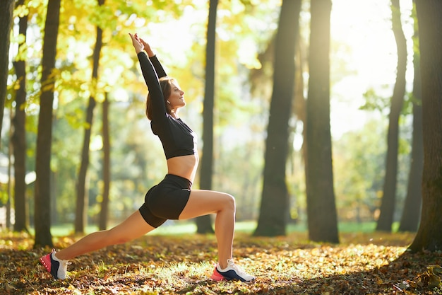 Aktive frau macht dehnübungen für den körper im freien