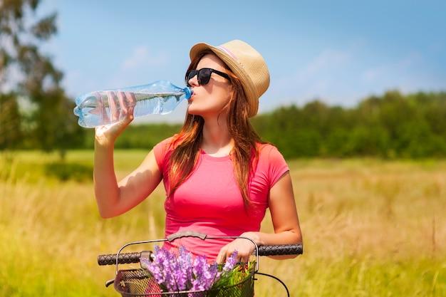 Aktive frau mit fahrrad, die kaltes wasser trinkt