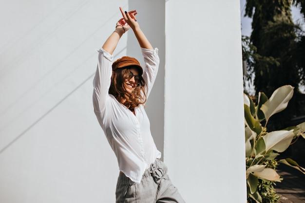 Aktive frau mit welligem haar in sonnenbrille tanzt auf der straße neben weißem gebäude, umgeben von bäumen.