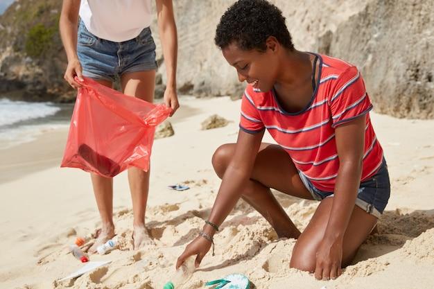 Aktive frauen reinigen den strand von müll