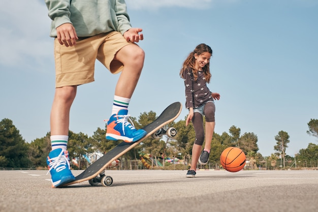 Aktive freunde im teenageralter, die skateboard fahren und mit basketballball spielen