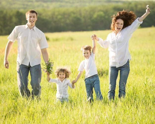 Aktive glückliche familie, die draußen im grünen feld des frühlinges springt