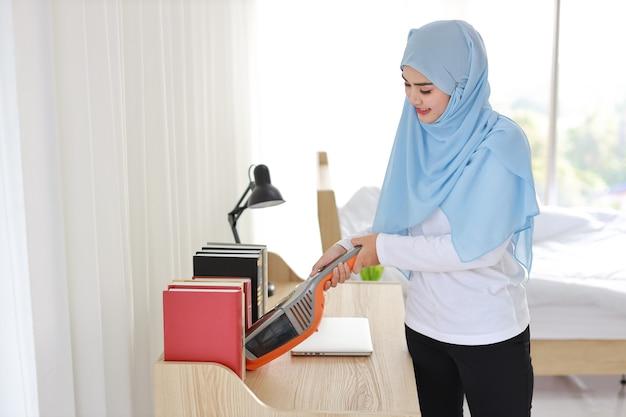 Aktive junge asiatische muslimische hausfrau frau reinigung mit staubsauger holztisch mit computer. putzendes mädchen im weißen kleid und in den schwarzen leggings, die ihr zimmer staubsaugen