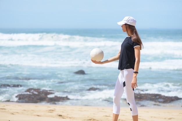 Aktive junge frau am strand mit volleyball ball