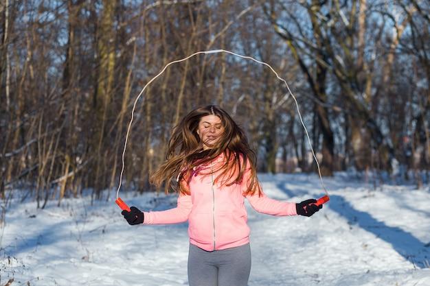 Aktive junge frau führt eine übung mit einem springseil durch