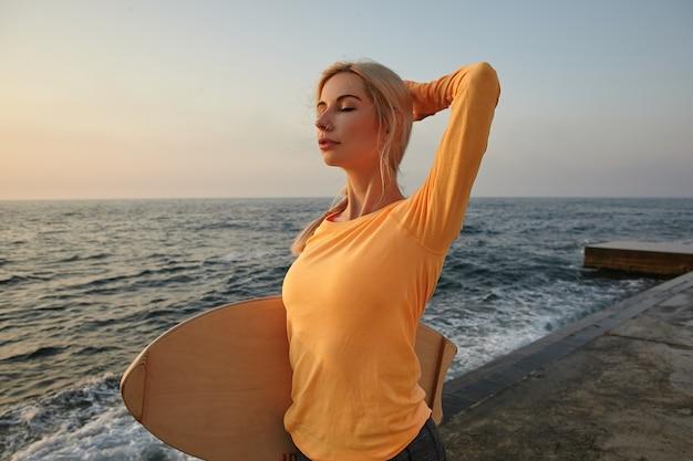 Aktive junge frau mit blondem haar, das am frühen morgen über meerblick aufwirft, orange langarmoberteil trägt, holzbrett hält und hand auf ihrem hinterkopf hält