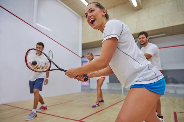 Aktive junge leute, die squash spielen