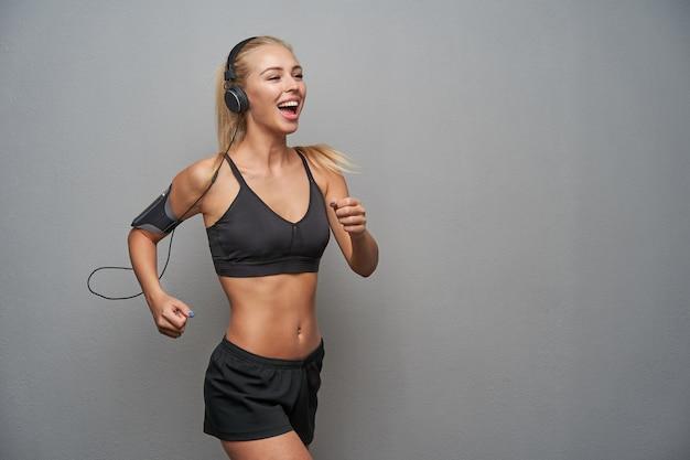 Aktive junge schlanke blonde frau mit lässiger frisur, die sportliche kleidung trägt, während sie drinnen läuft, musik in kopfhörern hört und glücklich lächelt, während sie über hellgrauem hintergrund posiert