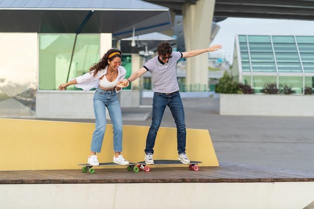 Aktive junge skaterpaare lernen, zusammen longboard zu fahren, halten die hände lachend auf dem skateboard