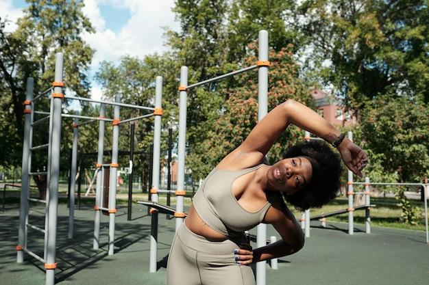 Aktive junge sportlerin, die im freien seitenbiegungen macht
