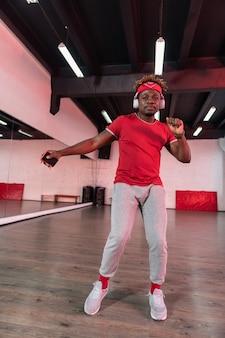 Aktive junge tänzerin, die sich mit smartphone in einer hand und kopfhörern an den ohren bewegt